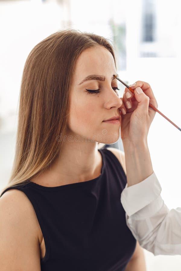 Πορτρέτο ενός όμορφου κοριτσιού πελατών κατά τη διάρκεια μιας διαδικασίας διορθώσεων φρυδιών στοκ φωτογραφίες