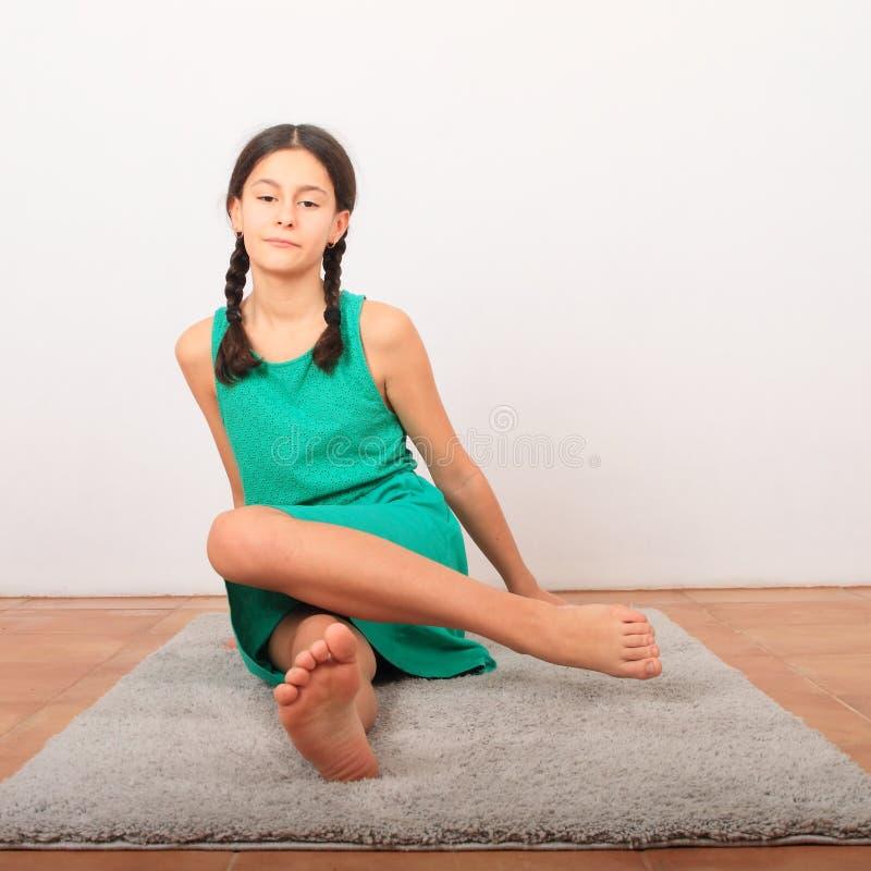 Πορτρέτο ενός όμορφου κοριτσιού που κάθεται σε γκρι χαλί στοκ εικόνες