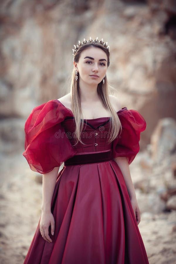 Πορτρέτο ενός όμορφου κοριτσιού σε ένα κόκκινο φόρεμα και μια κορώνα στοκ φωτογραφίες με δικαίωμα ελεύθερης χρήσης