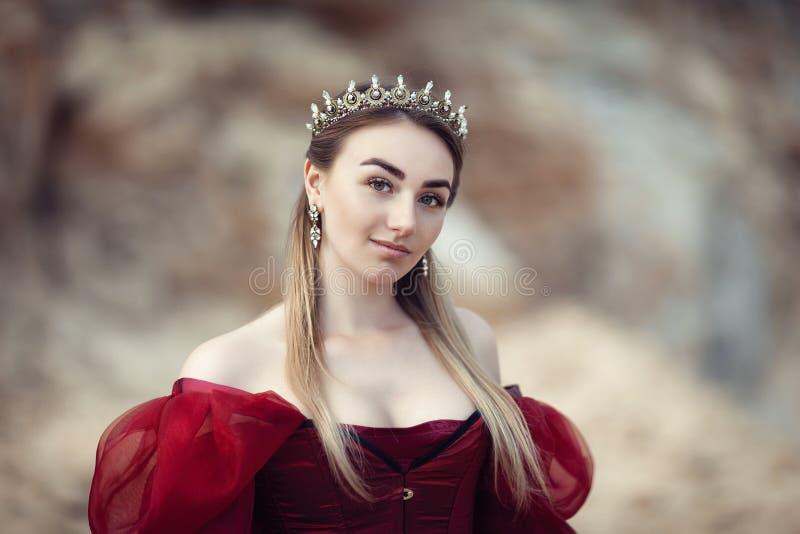 Πορτρέτο ενός όμορφου κοριτσιού σε ένα κόκκινο φόρεμα και μια κορώνα στοκ εικόνες