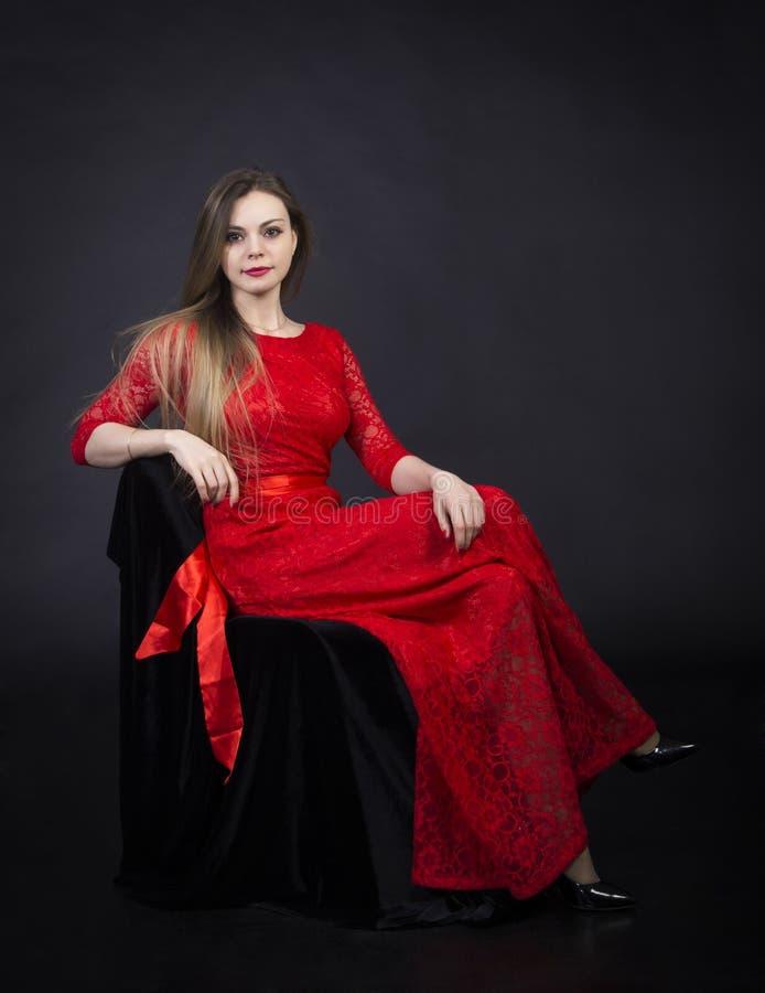 Πορτρέτο ενός όμορφου κοριτσιού σε ένα κόκκινο φόρεμα στοκ εικόνα
