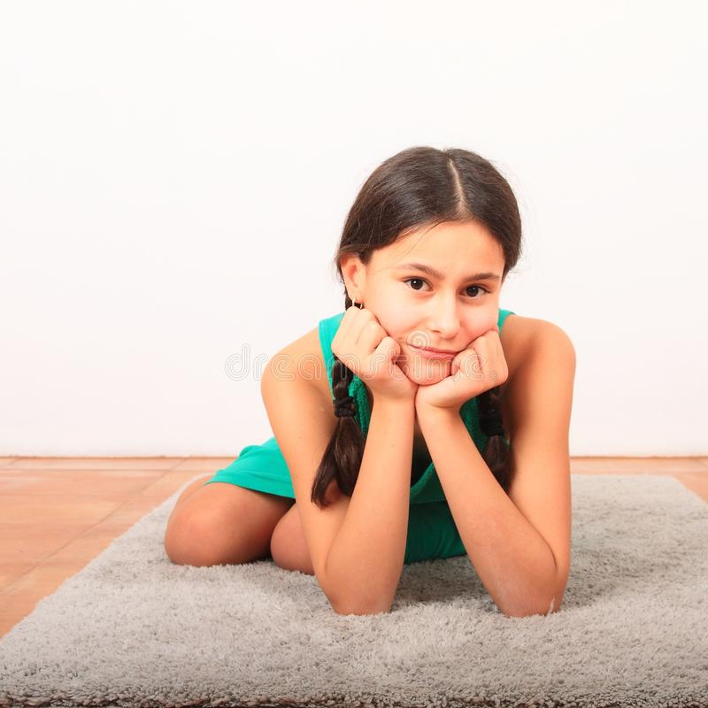 Πορτρέτο ενός όμορφου κοριτσιού σε γκρι χαλί στοκ φωτογραφία