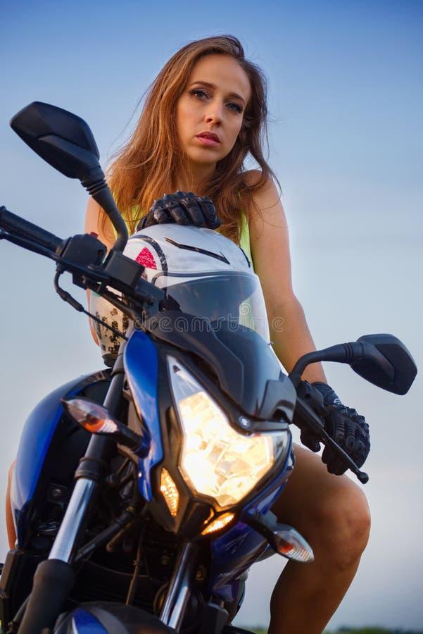 Πορτρέτο ενός όμορφου κοριτσιού σε μια αθλητική μοτοσικλέτα στοκ εικόνες