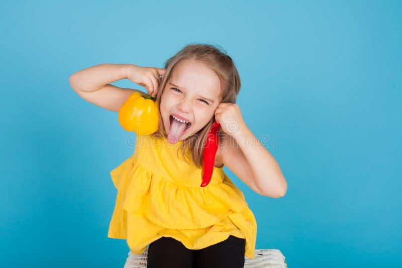Πορτρέτο ενός όμορφου μικρού κοριτσιού με το κίτρινο και κόκκινο πιπέρι φρέσκων λαχανικών στοκ φωτογραφίες