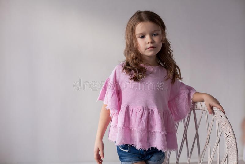 Πορτρέτο ενός όμορφου μικρού κοριτσιού σε ένα ρόδινο φόρεμα πέντε έτη στοκ εικόνα