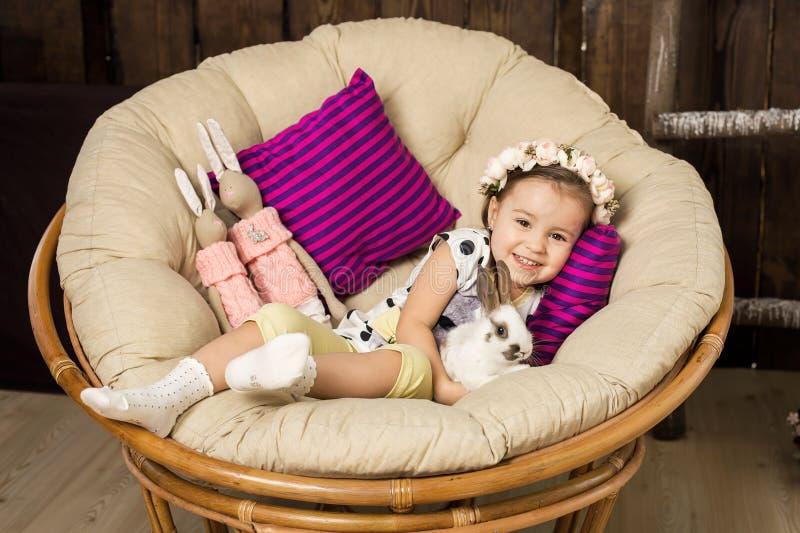 Πορτρέτο ενός όμορφου μικρού κοριτσιού σε ένα στεφάνι των λουλουδιών Ένα κορίτσι με ένα χαριτωμένο χνουδωτό άσπρο λαγουδάκι Πάσχα στοκ εικόνες