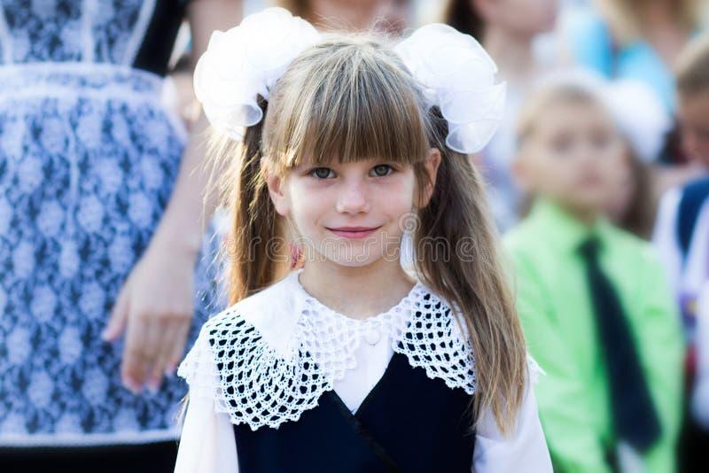 Πορτρέτο ενός όμορφου μικρού κοριτσιού σε ένα σχολικό φόρεμα και στα τόξα Πρώτη τάξη στοκ εικόνα