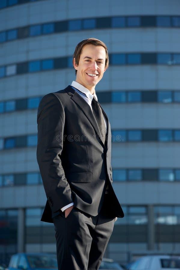 Πορτρέτο ενός όμορφου νέου επιχειρησιακού ατόμου που χαμογελά έξω από το γραφείο στοκ φωτογραφία με δικαίωμα ελεύθερης χρήσης
