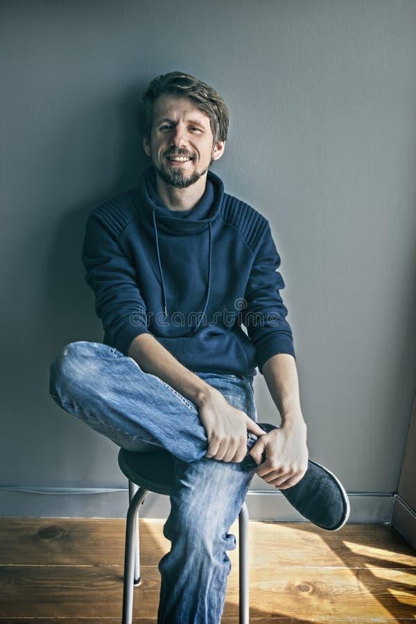 Πορτρέτο ενός όμορφου νεαρού άνδρα που χαμογελά ενάντια στο μπλε γκρίζο backg στοκ φωτογραφίες με δικαίωμα ελεύθερης χρήσης