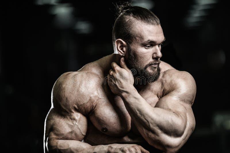 Πορτρέτο ενός όμορφου τύπου σε ένα υπόβαθρο της γυμναστικής στοκ φωτογραφία