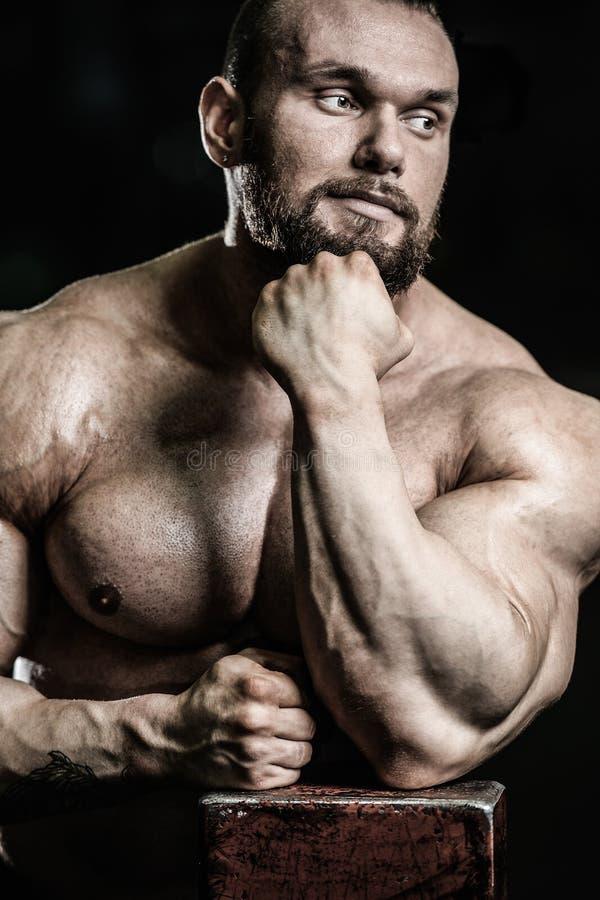 Πορτρέτο ενός όμορφου τύπου σε ένα υπόβαθρο της γυμναστικής στοκ εικόνα