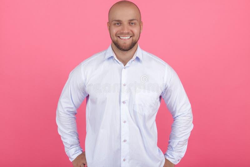 Πορτρέτο ενός όμορφου φαλακρού γενειοφόρου ατόμου στέκεται και χαμογελά στη κάμερα και κρατά τα όπλα του λοξά απομονωμένος στο ρό στοκ φωτογραφία με δικαίωμα ελεύθερης χρήσης