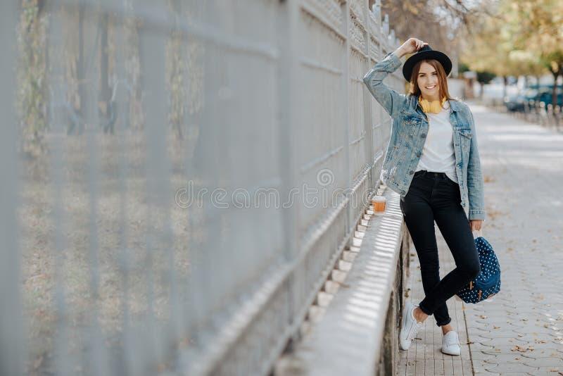 Πορτρέτο ενός όμορφου χαμογελώντας hipster κοριτσιού με την καφετιά τρίχα που φορά ένα καπέλο και που εξετάζει τη κάμερα υπαίθρια στοκ εικόνα με δικαίωμα ελεύθερης χρήσης