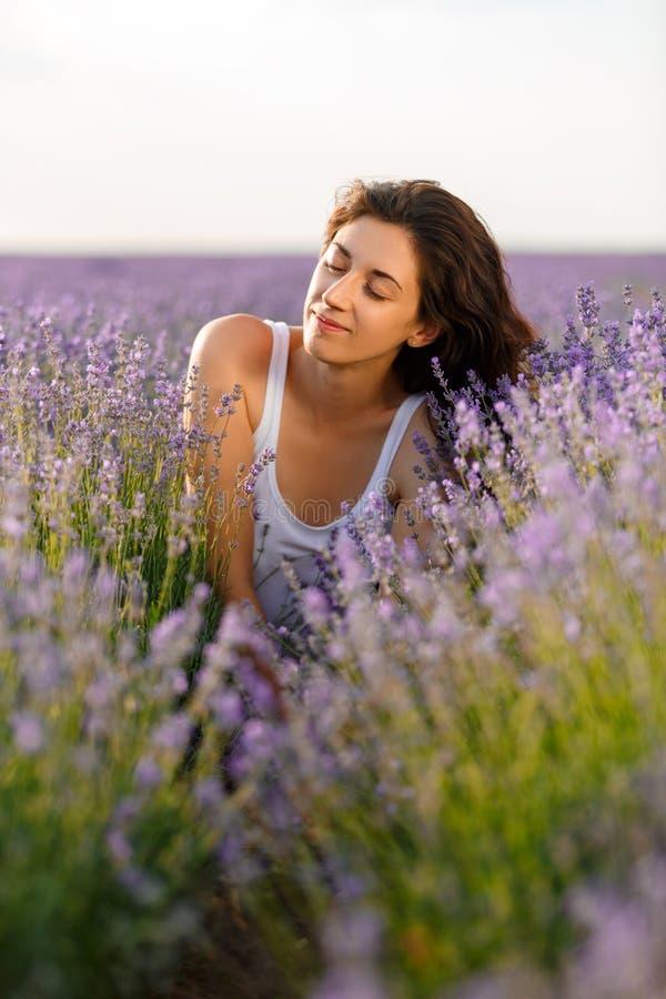 Πορτρέτο ενός όμορφου brunette σε έναν lavender τομέα Έκλεισε τα μάτια της στην ευχαρίστηση στοκ εικόνες