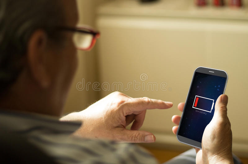 Πορτρέτο ενός ώριμου ατόμου με το χαμηλό κινητό τηλέφωνο μπαταριών στοκ εικόνα με δικαίωμα ελεύθερης χρήσης