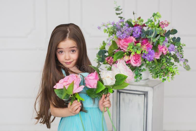 Πορτρέτο ενός brunete όμορφου μικρού κοριτσιού σε ένα τυρκουάζ φόρεμα με την επερώτηση της ματιάς στοκ εικόνα με δικαίωμα ελεύθερης χρήσης