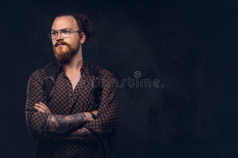 Πορτρέτο ενός redhead σπουδαστή hipster στα γυαλιά που ντύνονται σε ένα καφετί πουκάμισο, κρατά ένα σακίδιο πλάτης, που θέτει σε  στοκ εικόνα