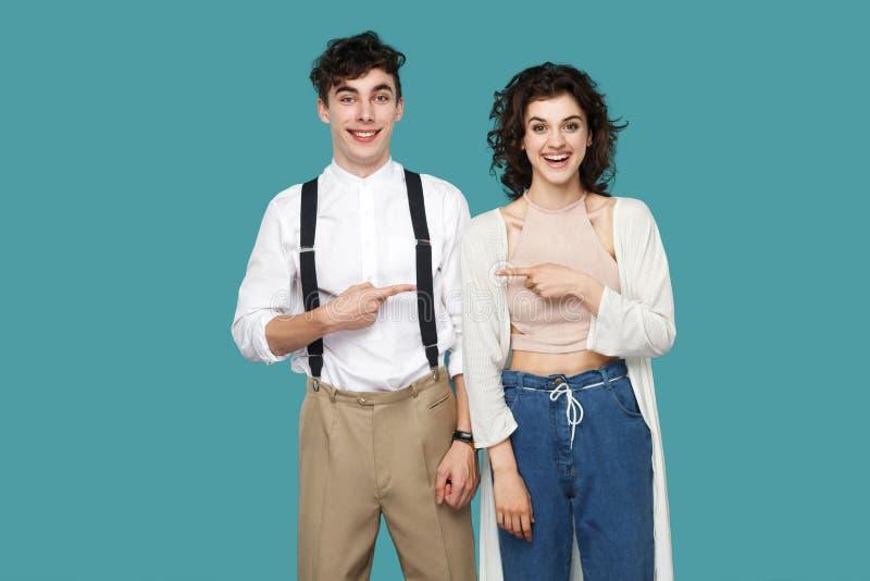_πορτρέτο ευτυχής επιτυχής δύο brunette μοντέρνος συνεργάτης, ζεύγος ή φίλος στέκομαι και δείχνω μεταξύ τους και κοιτάζω  στοκ φωτογραφίες