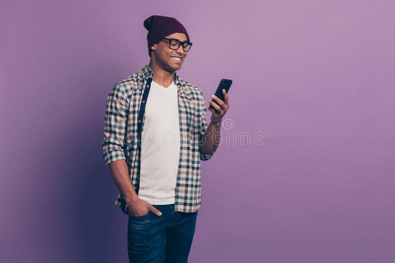 Πορτρέτο εύθυμου θετικού χιλιετούς με την ακτινοβολία του οδοντωτού χαμόγελου που χρησιμοποιεί τη σύγχρονη συσκευή συσκευών εκμετ στοκ φωτογραφία με δικαίωμα ελεύθερης χρήσης