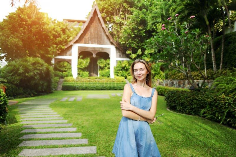 Πορτρέτο ηλιοφάνειας της νέας γυναίκας που εξετάζει τη κάμερα που χαμογελά στους πράσινους φοίνικες και το υπόβαθρο σπιτιών στην  στοκ φωτογραφίες με δικαίωμα ελεύθερης χρήσης
