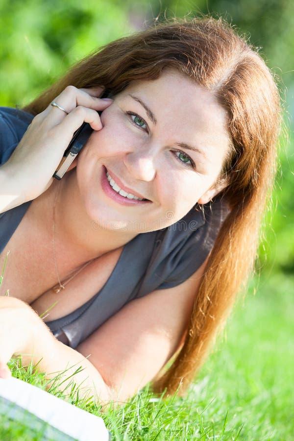 Πορτρέτο θερινών κινηματογραφήσεων σε πρώτο πλάνο της όμορφης νέας γυναίκας με το κινητό τηλέφωνο στη χλόη στοκ εικόνα