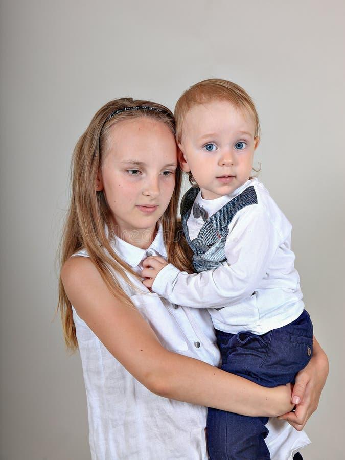 Πορτρέτο κινηματογραφήσεων σε πρώτο πλάνο ενός αδελφού και μιας αδελφής μικρό παιδί που αγκαλιάζει την παλαιότερη αδελφή του στοκ φωτογραφία
