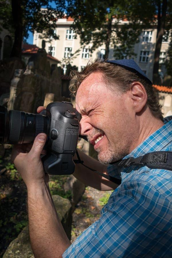 Πορτρέτο κινηματογραφήσεων σε πρώτο πλάνο ενός αρσενικού φωτογράφου τουριστών με ένα εβραϊκό καπέλο που κρατά μια κάμερα που παίρ στοκ φωτογραφίες