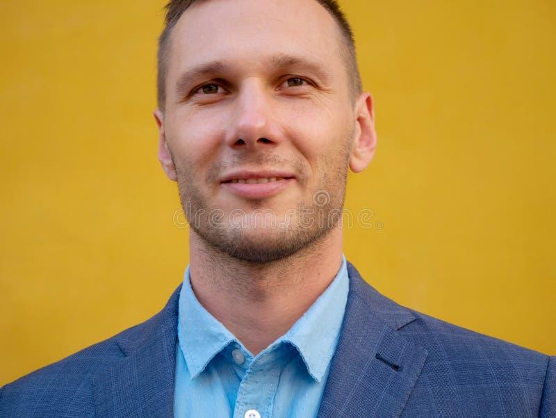 Πορτρέτο κινηματογραφήσεων σε πρώτο πλάνο ενός χαμογελώντας επιχειρηματία πέρα από το κίτρινο υπόβαθρο στοκ φωτογραφία