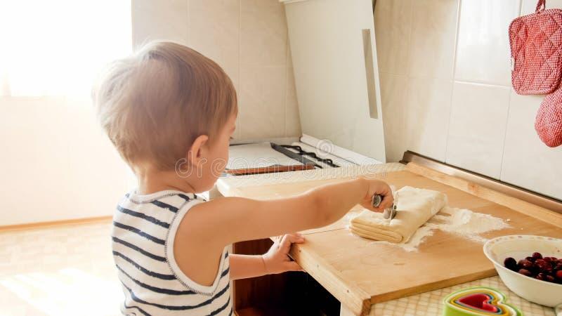 Πορτρέτο κινηματογραφήσεων σε πρώτο πλάνο λατρευτών 3 χρονών μπισκότων ψησίματος αγοριών μικρών παιδιών και της κυλώντας ζύμης με στοκ φωτογραφία