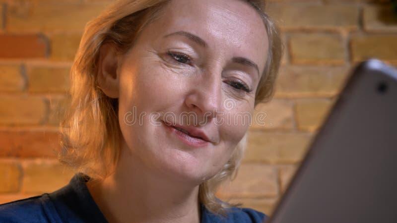 Πορτρέτο κινηματογραφήσεων σε πρώτο πλάνο της ανώτερης καυκάσιας κυρίας που εργάζεται προσεκτικά και πρόθυμα με την ταμπλέτα στην στοκ εικόνες