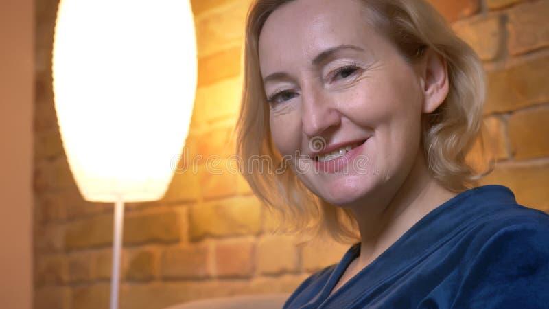 Πορτρέτο κινηματογραφήσεων σε πρώτο πλάνο της ανώτερης καυκάσιας γυναικείας προσοχής πρόθυμα στη κάμερα στην άνετη εγχώρια ατμόσφ στοκ φωτογραφίες με δικαίωμα ελεύθερης χρήσης