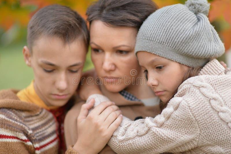 Πορτρέτο κινηματογραφήσεων σε πρώτο πλάνο της λυπημένης μητέρας με τα παιδιά υπαίθρια στοκ εικόνες