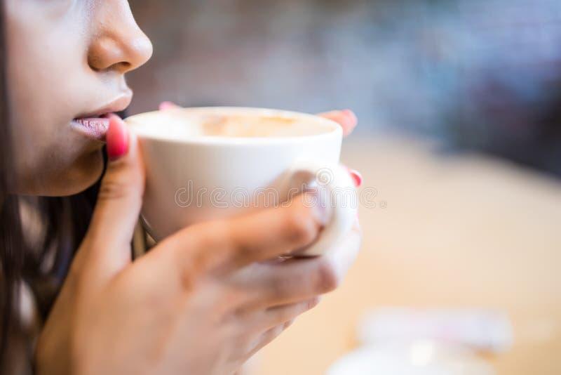 Πορτρέτο κινηματογραφήσεων σε πρώτο πλάνο της νέας γυναίκας με το ποτό καφέ στοκ φωτογραφία