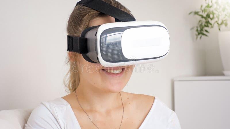 Πορτρέτο κινηματογραφήσεων σε πρώτο πλάνο της νέας γυναίκας που φορά το κράνος εικονικής πραγματικότητας στο σπίτι στοκ εικόνα