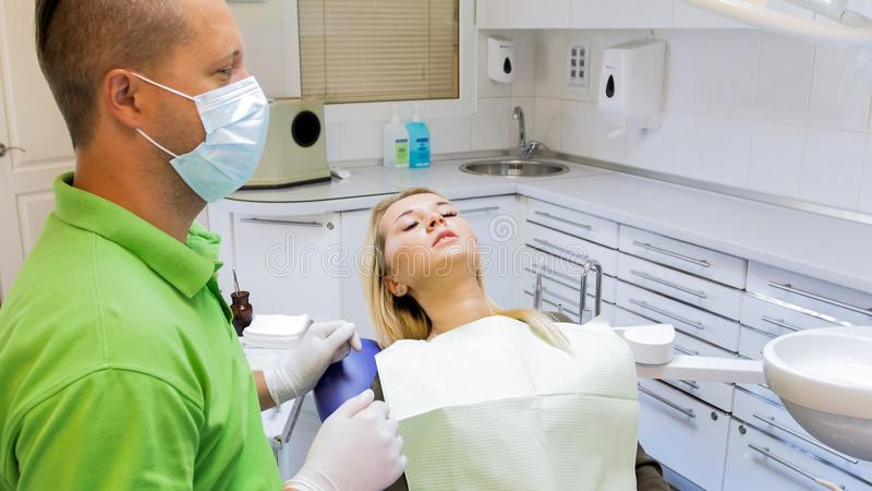 Πορτρέτο κινηματογραφήσεων σε πρώτο πλάνο της νέας φοβησμένης συναίσθημα συνεδρίασης γυναικών στην καρέκλα οδοντιάτρων στοκ εικόνα