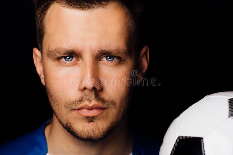 Πορτρέτο κινηματογραφήσεων σε πρώτο πλάνο της νέας όμορφης τοποθέτησης ποδοσφαίρου ποδοσφαιριστών στο σκοτεινό υπόβαθρο στοκ εικόνα με δικαίωμα ελεύθερης χρήσης