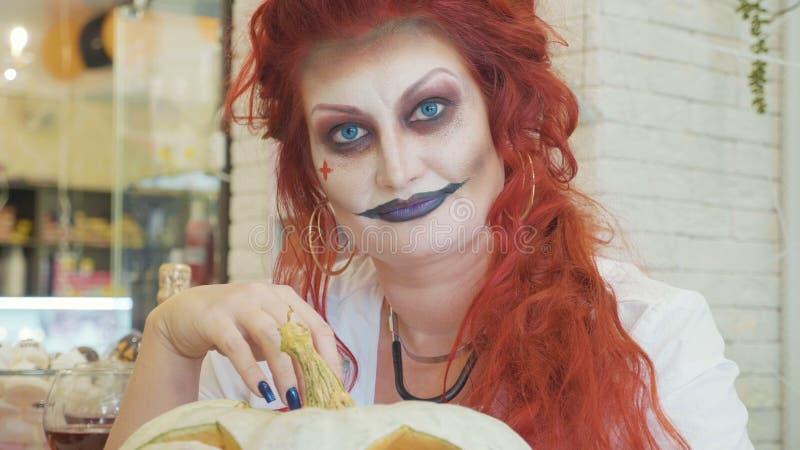 Πορτρέτο κινηματογραφήσεων σε πρώτο πλάνο της redhead γυναίκας με αποκριές makeup με την κολοκύθα στοκ εικόνα με δικαίωμα ελεύθερης χρήσης