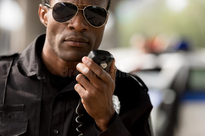 πορτρέτο κινηματογραφήσεων σε πρώτο πλάνο του αστυνομικού αφροαμερικάνων που μιλά από walkie-talkie στοκ φωτογραφίες με δικαίωμα ελεύθερης χρήσης
