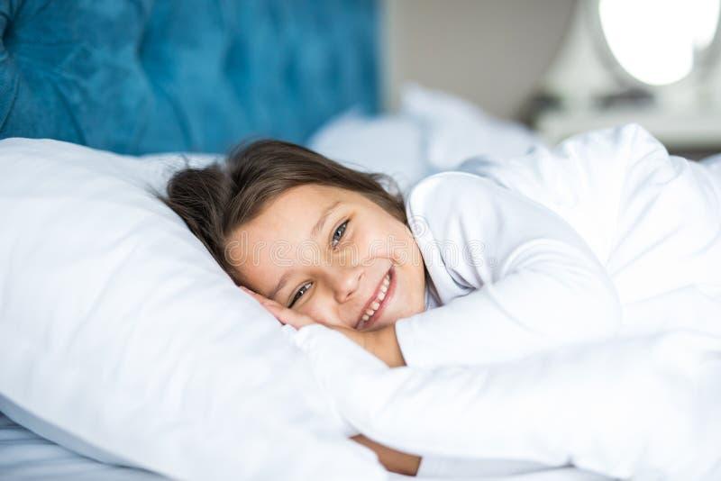 Πορτρέτο κινηματογραφήσεων σε πρώτο πλάνο του γελώντας μικρού κοριτσιού που βρίσκεται στο κρεβάτι με το χέρι κάτω από το μαξιλάρι στοκ εικόνες