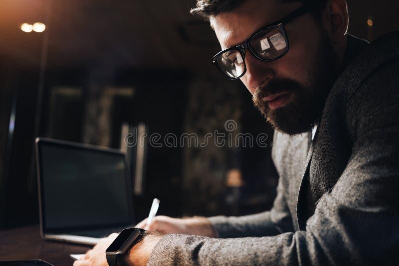 Πορτρέτο κινηματογραφήσεων σε πρώτο πλάνο του γενειοφόρου επιχειρηματία στο γραφείο σοφιτών γυαλιών τη νύχτα Δημιουργικός διευθυν στοκ φωτογραφία