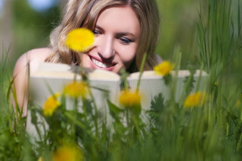 Πορτρέτο κινηματογραφήσεων σε πρώτο πλάνο του ευτυχούς καυκάσιου θηλυκού με την ανάγνωση βιβλίων υπαίθρια στο χορτοτάπητα στοκ εικόνα