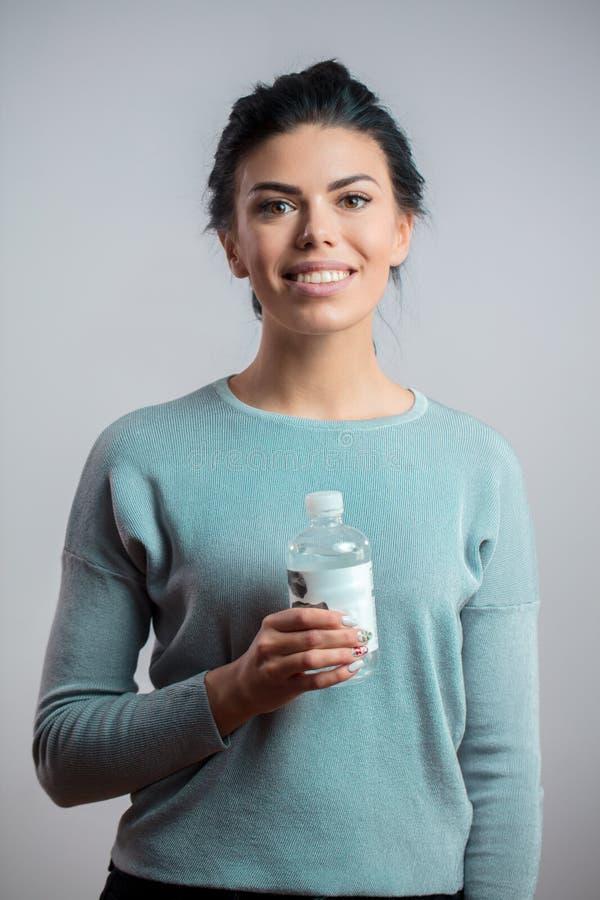 Πορτρέτο κινηματογραφήσεων σε πρώτο πλάνο του ευτυχούς νέου θηλυκού που κρατά ένα μπουκάλι νερό στοκ εικόνα με δικαίωμα ελεύθερης χρήσης