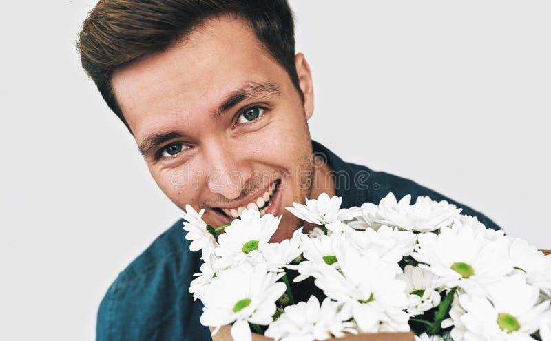 Πορτρέτο κινηματογραφήσεων σε πρώτο πλάνο του ευτυχούς όμορφου ατόμου που χαμογελά με μια ανθοδέσμη των άσπρων λουλουδιών Ελκυστι στοκ φωτογραφία με δικαίωμα ελεύθερης χρήσης