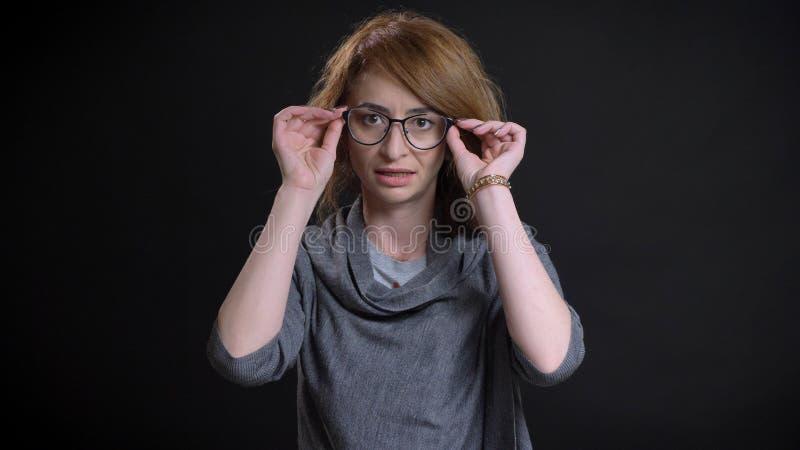 Πορτρέτο κινηματογραφήσεων σε πρώτο πλάνο του μέσης ηλικίας υπερβολικού redhead θηλυκού που εξετάζει ευθέος τη κάμερα που καθορίζ στοκ φωτογραφίες με δικαίωμα ελεύθερης χρήσης