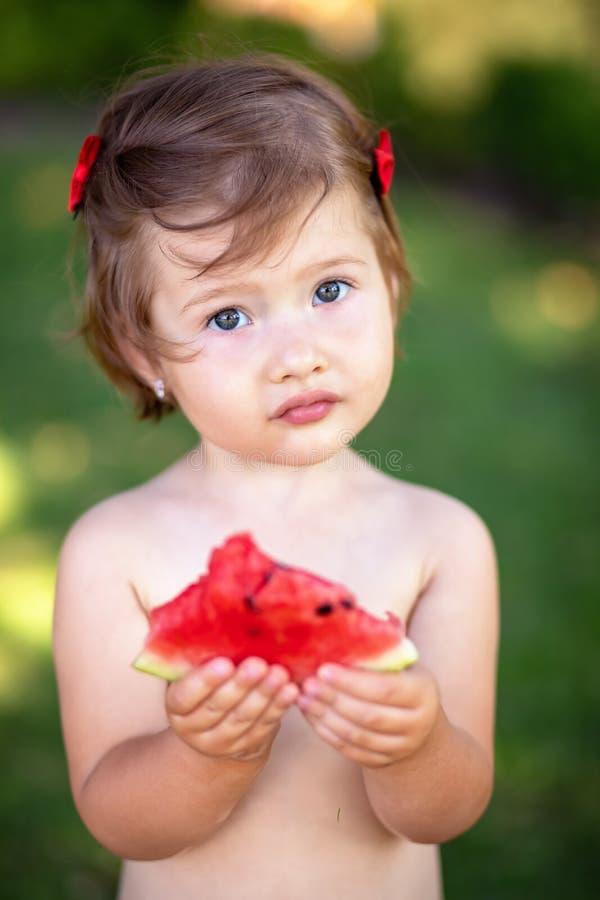 Πορτρέτο κινηματογραφήσεων σε πρώτο πλάνο του χαριτωμένου μικρού κοριτσιού που τρώει το καρπούζι στη χλόη στο υγιές πρόχειρο φαγη στοκ εικόνα