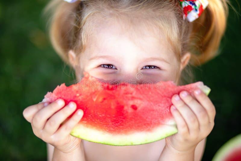 Πορτρέτο κινηματογραφήσεων σε πρώτο πλάνο του χαριτωμένου μικρού κοριτσιού που τρώει το καρπούζι στη χλόη στο καλοκαίρι στοκ εικόνες με δικαίωμα ελεύθερης χρήσης