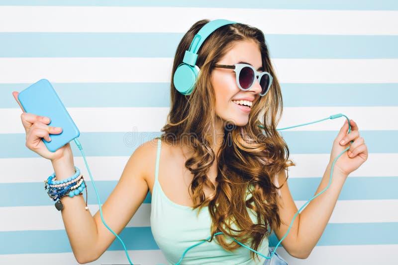 Πορτρέτο κινηματογραφήσεων σε πρώτο πλάνο του χαρούμενου κοριτσιού που απολαμβάνει τη μουσική στα μεγάλα ακουστικά, που κρατά το  στοκ εικόνα με δικαίωμα ελεύθερης χρήσης