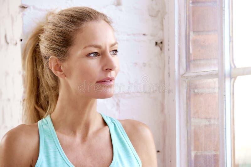 Πορτρέτο κινηματογραφήσεων σε πρώτο πλάνο του όμορφου κοιτάγματος γυναικών έξω το παράθυρο και της χαλάρωσης μετά από το workout στοκ φωτογραφία με δικαίωμα ελεύθερης χρήσης