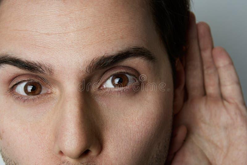 Πορτρέτο κινηματογραφήσεων σε πρώτο πλάνο του όμορφου νεαρού άνδρα που προσπαθεί να ακούσει τη συνομιλία κάποιου στοκ φωτογραφία με δικαίωμα ελεύθερης χρήσης