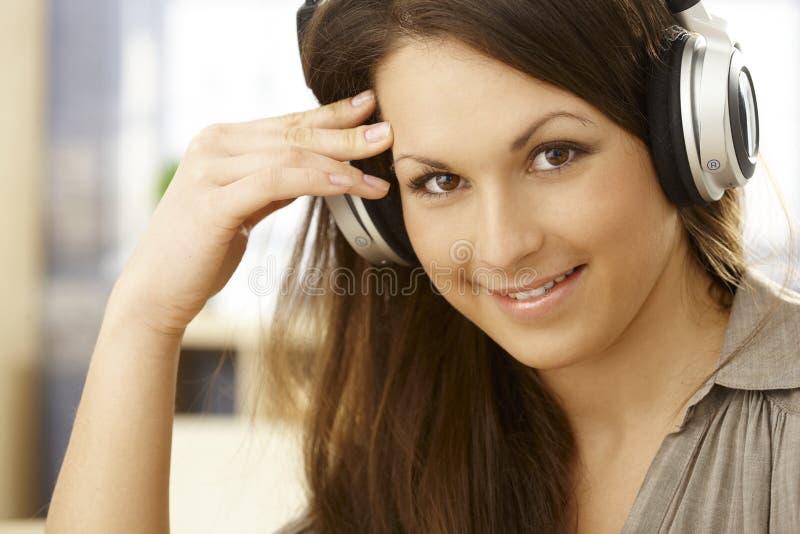 Πορτρέτο κινηματογραφήσεων σε πρώτο πλάνο της ευτυχούς γυναίκας με τα ακουστικά στοκ εικόνες με δικαίωμα ελεύθερης χρήσης